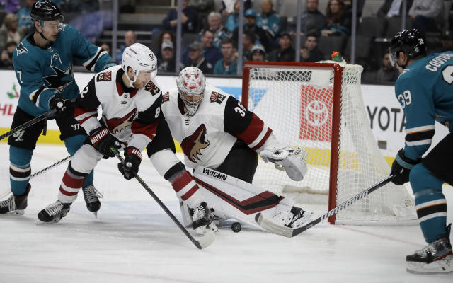 Arizona Coyotes goalie Darcy Kuemper (35) and Jordan Oesterle block a shot from San Jose Sharks' Logan Couture, right, during the first period of an NHL hockey game Tuesday, Dec. 17, 2019, in San Jose, Calif. (AP Photo/Ben Margot)