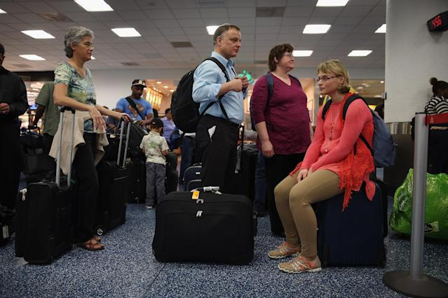 MIAMI, FL - APRIL 16: American Airlines passengers Arne Jahn (C), Monika Jahn (2nd R) and Inga Jahn (R) wait in line to get their tickets at Miami International Airport on April 16, 2013 in Miami, Florida. Thousands of American Airlines travelers became stranded today when the airline was forced to ground all its flights after a nationwide problem with its computer systems (Photo by Joe Raedle/Getty Images)