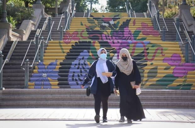 Two people wearing masks cross Sussex Street in Ottawa earlier this week. (Trevor Pritchard/CBC - image credit)