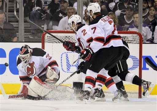 New Jersey Devils goalie Martin Brodeur (30) makes a save as New Jersey Devils defenseman Marek Zidlicky (2) and New Jersey Devils defenseman Henrik Tallinder (7) look on in the first period against the Los Angeles Kings during Game 6 of the NHL hockey Stanley Cup finals,Monday, June 11, 2012, in Los Angeles. (AP Photo/Mark J. Terrill)