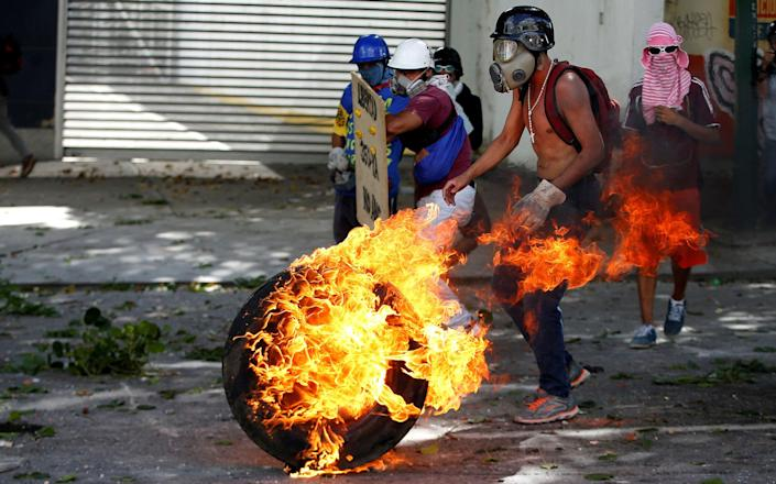 <p>Demonstrators use a tire on fire to block a street at a rally during a strike called to protest against Venezuelan President Nicolas Maduro's government in Caracas, Venezuela, July 26, 2017. (Photo: Andres Martinez Casares/Reutes) </p>