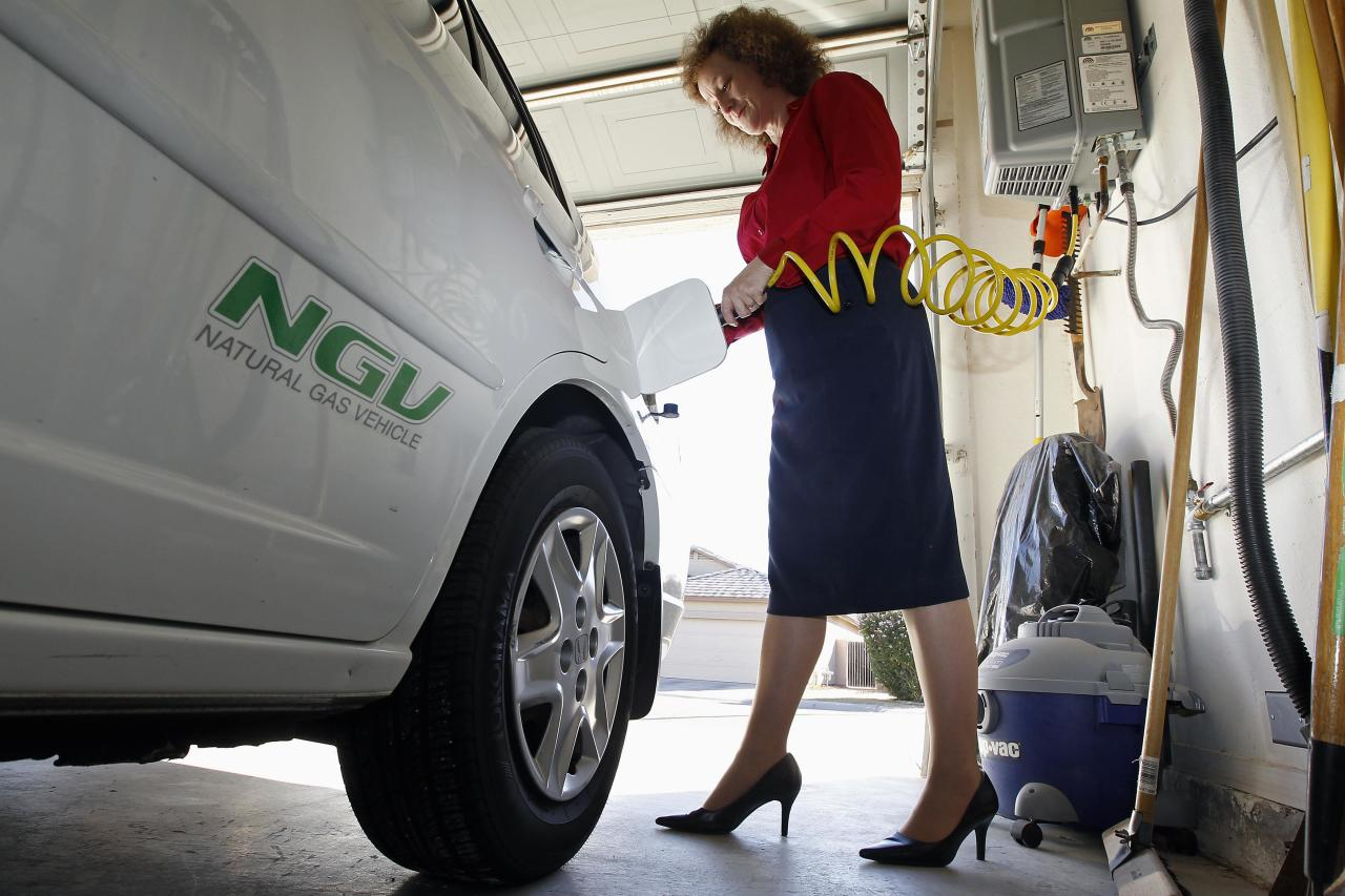Connie Jones connects the nozzle of a home refueling station to her 2003 natural gas powered Honda Civic in the garage of her home in Chandler, Arizona, October 3, 2013. Home refueling units, which tap into a house natural gas main and compress the fuel so it can fill a vehicle tank overnight, have been available for years. With natural gas at $1.40 per equivalent gallon, it costs the Joneses $30 to drive their Honda Civic GX 1,200 miles (1,930 km) each month, about $130 less than an average gasoline car covering the same distance. Picture taken October 3, 2013. To match Insight NATURALGAS/HOME-REFUELING REUTERS/Ralph D. Freso (UNITED STATES)