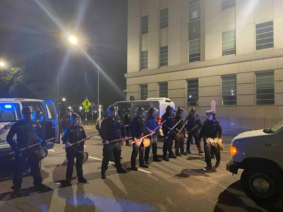 Police in riot gear respond during a march through downtown Raleigh on Sunday night, April 18, 2021.