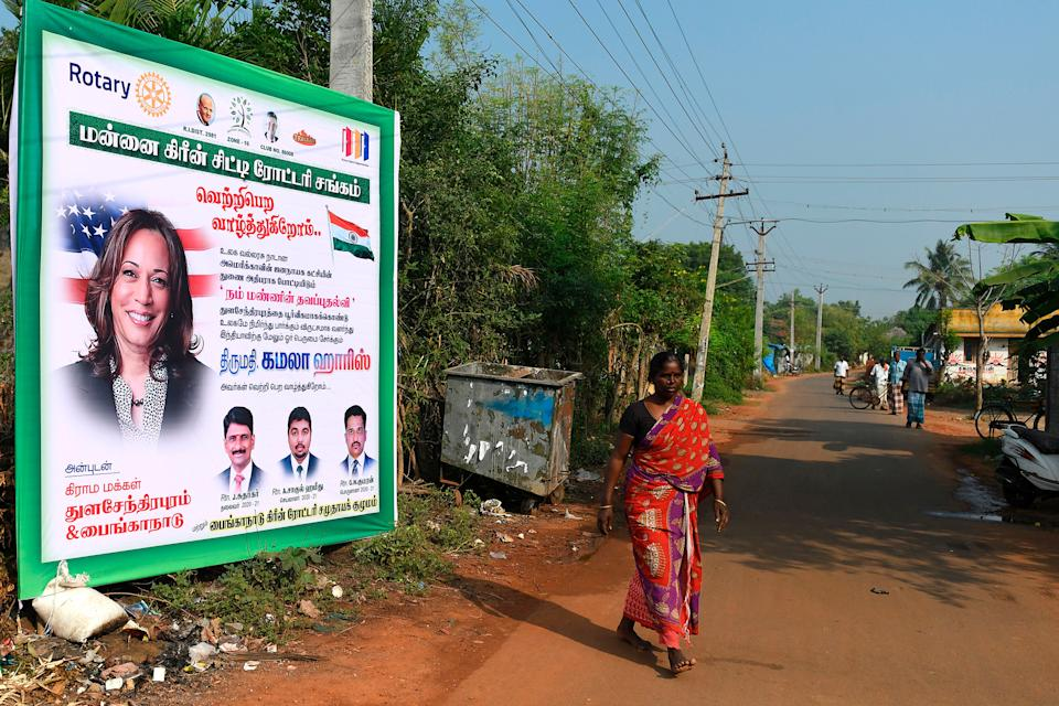"A woman walks past a poster of U.S. vice presidential candidate Kamala Harris at her ancestral village of Thulasendrapuram, Tamil Nadu, on Nov. 3.<span class=""copyright"">Arun Sankar—AFP/Getty Images</span>"
