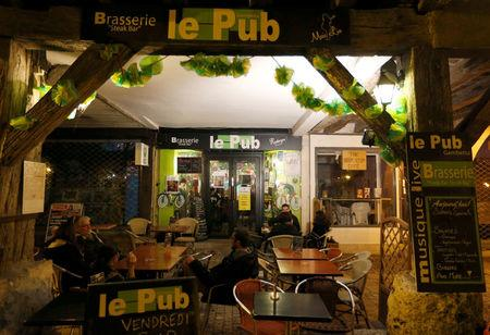 People sit on the terrace of 'le Pub' in Eymet, France, November 10, 2017. Britons in France are waiting anxiously for EU leaders to decide whether or not to approve a Brexit deal at a December 14-15 summit in Brussels. Picture taken November 10, 2017. REUTERS/Regis Duvignau