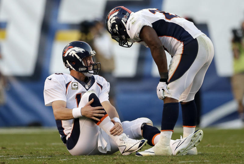 Denver Broncos quarterback Peyton Manning, left, holds his leg after being injured while playing the San Diego Chargers as teammate running back Knowshon Moreno, right, talks with him during the second half of a NFL football game on Sunday, Nov. 10, 2013, in San Diego. (AP Photo/Gregory Bull)
