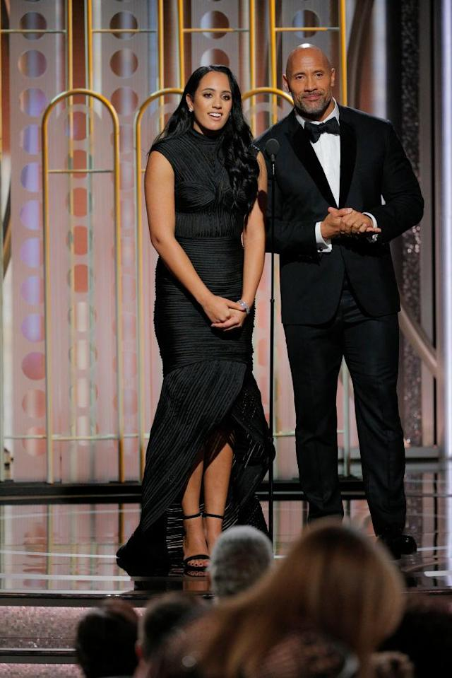 "Golden Globe Ambassador Simone Garcia Johnson and her popular dad, Dwayne ""The Rock"" Johnson, speak onstage during the Golden Globes. (Photo: Paul Drinkwater/NBCUniversal via Getty Images)"