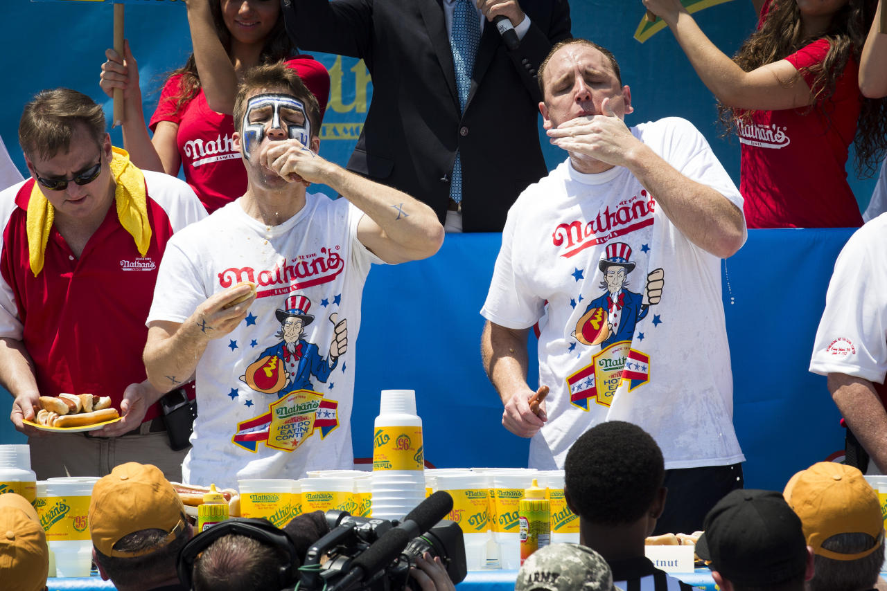 "Tim ""Eater X"" Janus, left, and five-time reigning champion Joey Chestnut, right, compete in the Nathan's Famous Hot Dog Eating World Championship, Wednesday, July 4, 2012, in the Brooklyn borough of New York. Chestnut won his sixth straight Coney Island hot dog eating contest.  (AP Photo/John Minchillo)"