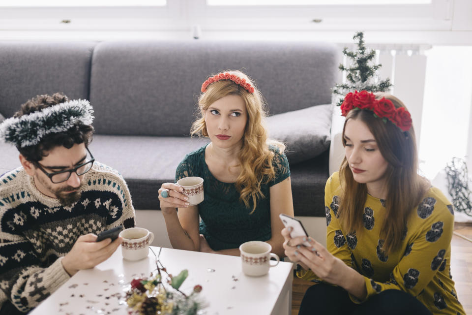Annoyed young woman sitting between her friends looking at her smartphones