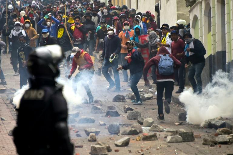 Demonstrators clash with riot police in Quito, as thousands march against President Lenin Moreno's decision to slash fuel subsidies (AFP Photo/Rodrigo BUENDIA)