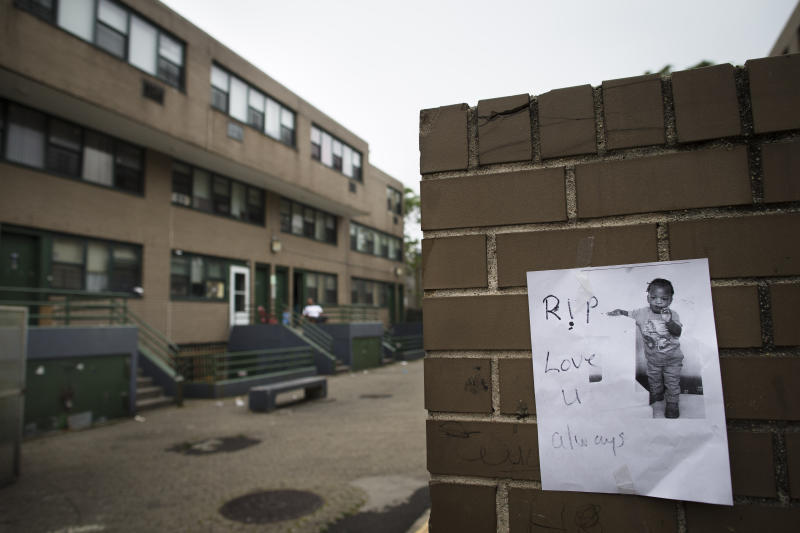 FILE - In this Sept. 2, 2013 file photo, a flyer bearing an image of Antiq Hennis, the 1-year-old boy who was shot in his stroller during a walk with his parents a day earlier, is posted on a wall outside an apartment complex, in the Brownsville neighborhood in the Brooklyn borough of New York. Strategies that have dropped crime to record lows across the city haven't taken hold in the Brooklyn neighborhood of Brownsville, where the cycle of violence, silence and retribution seems entrenched. And community activists say a big police presence can't make up for better schools, more jobs and better housing. (AP Photo/John Minchillo, File)