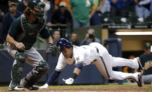 Milwaukee Brewers' Carlos Gomez slides safely home past Oakland Athletics catcher John Jaso for the winning run during the 10th inning of a baseball game Tuesday, June 4, 2013, in Milwaukee. Gomez scored from first on a hit by Yuniesky Betancourt. (AP Photo/Morry Gash)