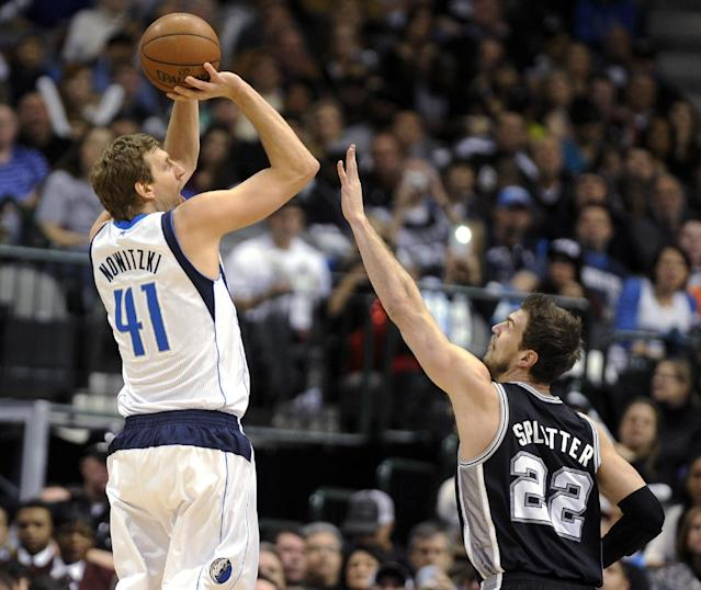 Dallas Mavericks forward Dirk Nowitzki (41) shoots over San Antonio Spurs center Tiago Splitter (22) during the first half of an NBA basketball game, Thursday, Dec. 26, 2013, in Dallas. (AP Photo/Matt Strasen)