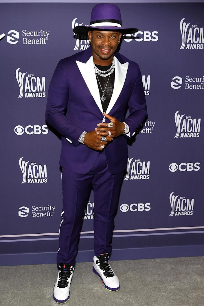 <p>teams his bright purple tux with white accents with a matching hat, double-strand necklace and statement rings. </p>