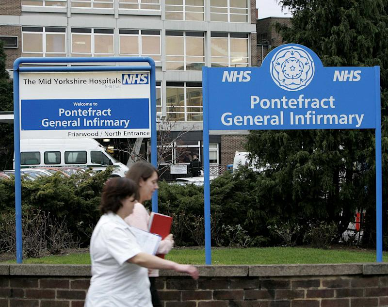 "Hospital workers walk past the front of Pontefract General Infirmary, northern England, where serial killer Harold Shipman murdered three patients whilst working as a junior doctor in the 1970s, January 27, 2005. Britain's ""Dr Death"", family physician Harold Shipman, who systematically murdered his patients, probably killed 250 people, an inquiry announced on Thursday after ruling the number of his victims was greater than originally thought. REUTERS/Ian Hodgson IH/ASA"