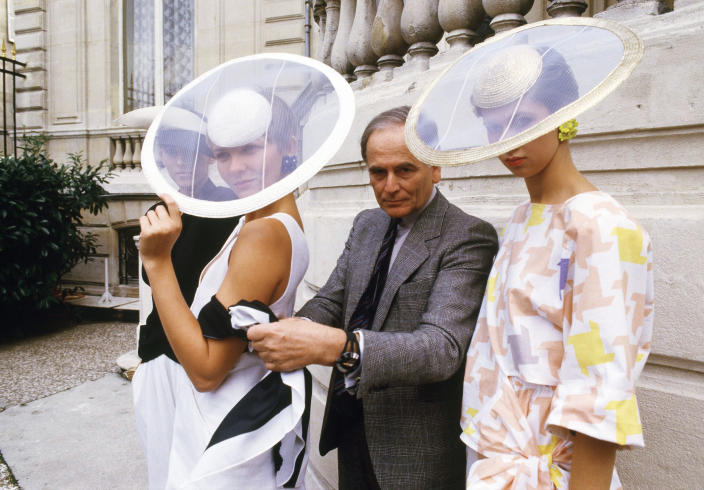 FILE - In this Sept.24, 1984 file photo, Paris couturier Pierre Cardin and models wearing ensembles from the summer 1985 ready-to-wear Cardin collection pose in Paris. France's Academy of Fine Arts says Pierre Cardin, the French designer whose Space Age style was among the iconic looks of 20th-century fashion, has died at 98. (AP Photo/Alexis Duclos, File)