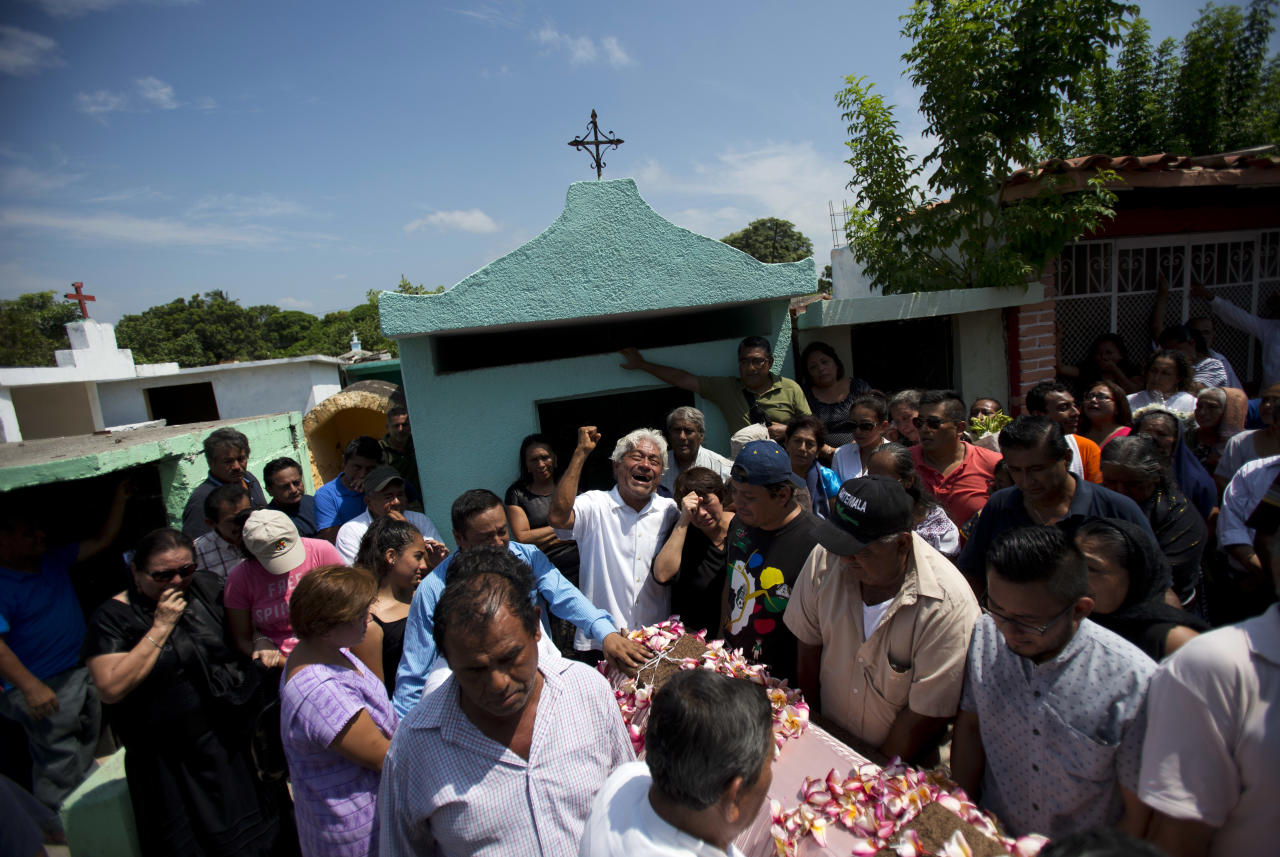 <p>A family member laments the death of 64-year-old Reynalda Matus, as mourners prepare to bury her at the Miercoles Santo Cemetery in Juchitan, Oaxaca state, Mexico, Saturday, Sept. 9, 2017. Matus was killed when the pharmacy where she worked nights collapsed during Thursday's massive earthquake. (AP Photo/Rebecca Blackwell) </p>