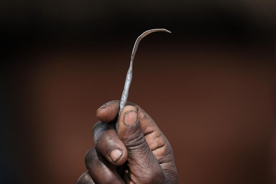 Ex-female genital mutilation (FGM) cutter Monika Cheptilak, who stopped practicing after the country set anti-FGM law in 2010, shows a homemade tool from a nail used for FGM, during the meeting of anti-FGM women group in Alakas village, bordering with Kenya, northeast Uganda on January 31, 2018. The UN estimates that over 200 million girls and women have experienced FGM which is a life-threatening procedure that involves the partial or total removal of a woman's external genitalia. February 6, 2018, marks the 6th International Day of Zero Tolerance for FGM. / AFP PHOTO / Yasuyoshi CHIBA        (Photo credit should read YASUYOSHI CHIBA/AFP via Getty Images)