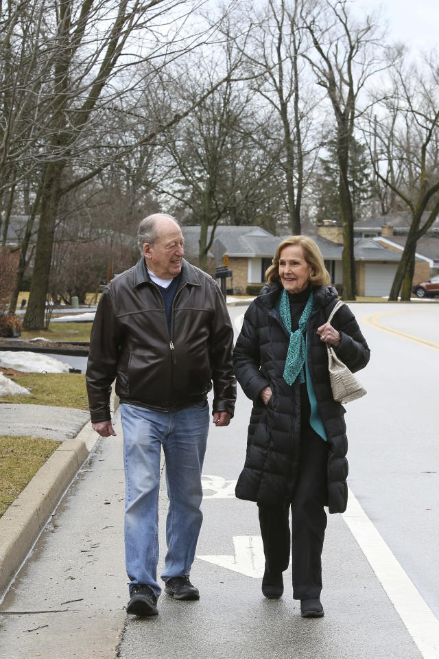 """Bill Gurolnick walks with his wife, Peggy Bartelstein, near their home in Northbrook, Ill., on Feb. 20, 2018. Gurolnick, who turns 87 in March 2018, thinks his own stellar memory is bolstered by keeping busy. He bikes, and plays tennis and water volleyball. He stays social through regular lunches and meetings with a men's group he co-founded. """"Absolutely that's a critical factor about keeping your wits about you,"""" exclaimed Gurolnick, fresh off his monthly gin game. (AP Photo/Teresa Crawford)"""
