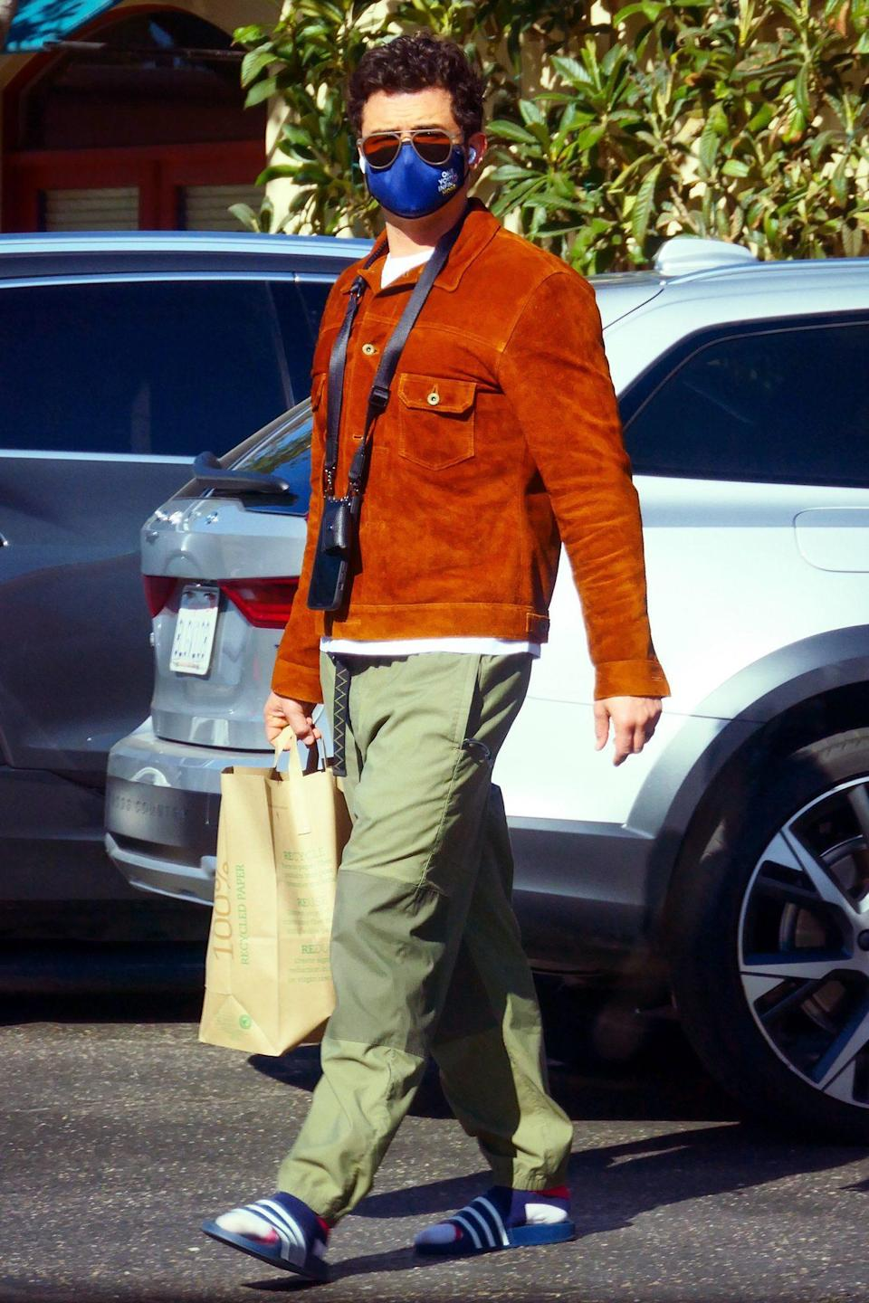 <p>Orlando Bloom puts on slides to go for a grocery run in Santa Barbara on Sunday.</p>