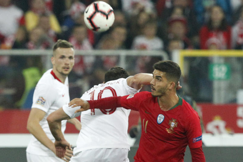 Poland's Grzegorz Krychowiak, center, hits Portugal's Andre Silva in his neck as they vie for the ball during the UEFA Nations League soccer match between Poland and Portugal at the Silesian Stadium Chorzow, Poland, Thursday Oct. 11, 2018. Krychowiak was shown a yellow card for the foul. (AP Photo/Czarek Sokolowski)