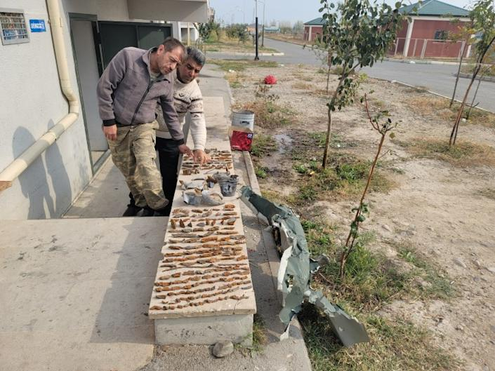 Wafadar Aliyev and Aydin Shahverdiyev, two refugees from the now Armenian-controlled district of Agdere — which Armenians call Martakert —, collect pieces of shrapnel from a barrage on their settlement near the city of Terter, Azerbaijan.