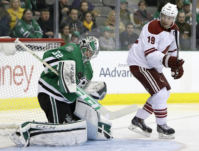 Phoenix Coyotes right wing Shane Doan (19) looks back to see Dallas Stars' Kari Lehtonen (32) stop a shot in the second period of an NHL hockey game, Saturday, Feb. 8, 2014, in Dallas. (AP Photo/Tony Gutierrez)