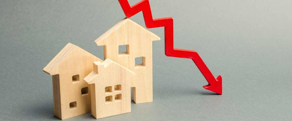Miniature wooden houses and a red arrow down. The concept of low mortgage rates.