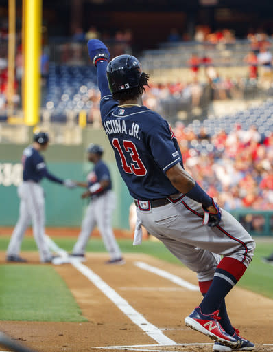 Atlanta Braves' Ronald Acuna Jr., right, reacts to scoring a run on a single by Freddie Freeman, left, during the first inning of a baseball game against the Philadelphia Phillies, Friday, July 26, 2019, in Philadelphia. (AP Photo/Chris Szagola)