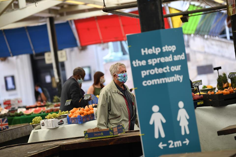 """People wearing face masks as a precaution against the transmission of the novel coronavirus shop at an open fruit and vegetable market in Leicester, central England on July 17, 2020, as local lockdown restrictions remain in force due to a spike in cases of the novel coronavirus in the city. - Boris Johnson said on July 17 he hoped Britain would """"return to normality"""" by November despite being badly affected by the coronavirus and predictions of a second wave of cases during winter months. The prime minister announced fresh powers for councils to impose  local lockdowns, such as one currently in place in the English midlands city of Leicester, if there were increased number of cases elsewhere. The government on July 16 annouced a partially ease a two-week-old local lockdown in Leicester, after the number of new coronavirus cases had fallen, but remained well above the average for England which means restrictions on schools, early years childcare and non-essential retail stores will be relaxed from July 24, but that other measures impacting travel, social gatherings and the hospitality sector would remain. (Photo by DANIEL LEAL-OLIVAS / AFP) (Photo by DANIEL LEAL-OLIVAS/AFP via Getty Images)"""