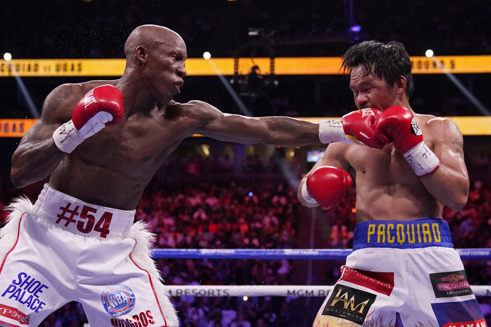 Yordenis Ugas, of Cuba, hits Manny Pacquiao, of the Philippines, in a welterweight championship boxing match Saturday, Aug. 21, 2021, in Las Vegas. (AP Photo/John Locher)