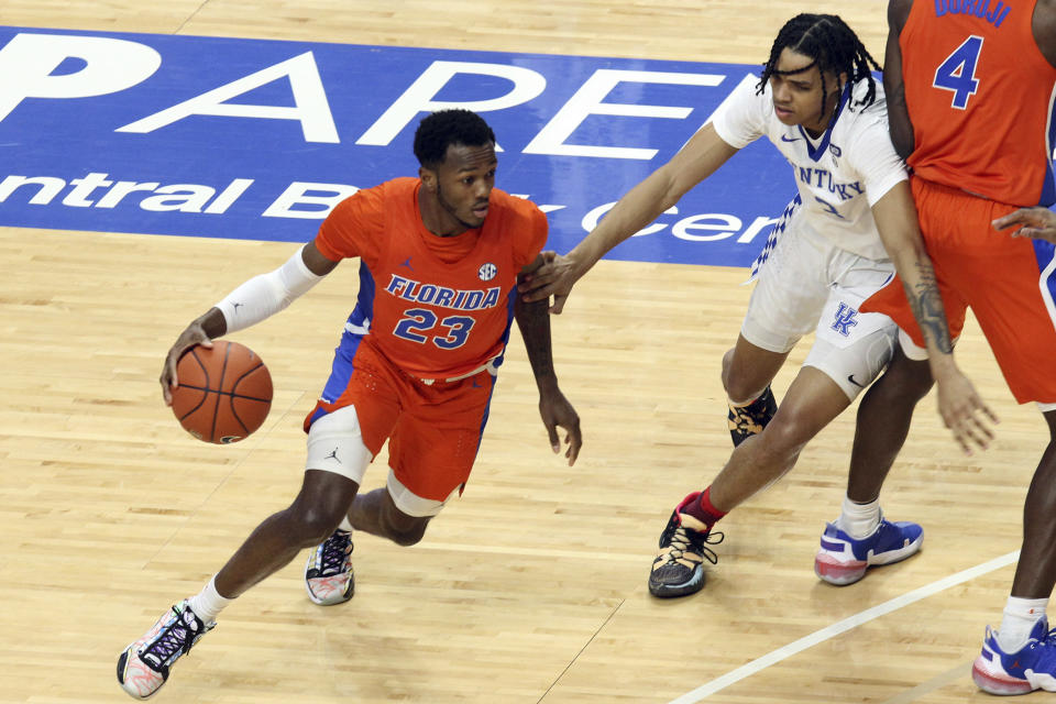 Florida's Scottie Lewis (23) drives near Kentucky's B.J. Boston (3) during the first half of an NCAA college basketball game in Lexington, Ky., Saturday, Feb. 27, 2021. (AP Photo/James Crisp)