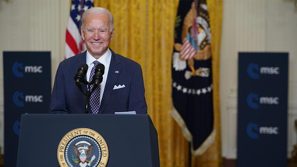President Biden smiles behind a podium that bears two microphones and the presidential seal.