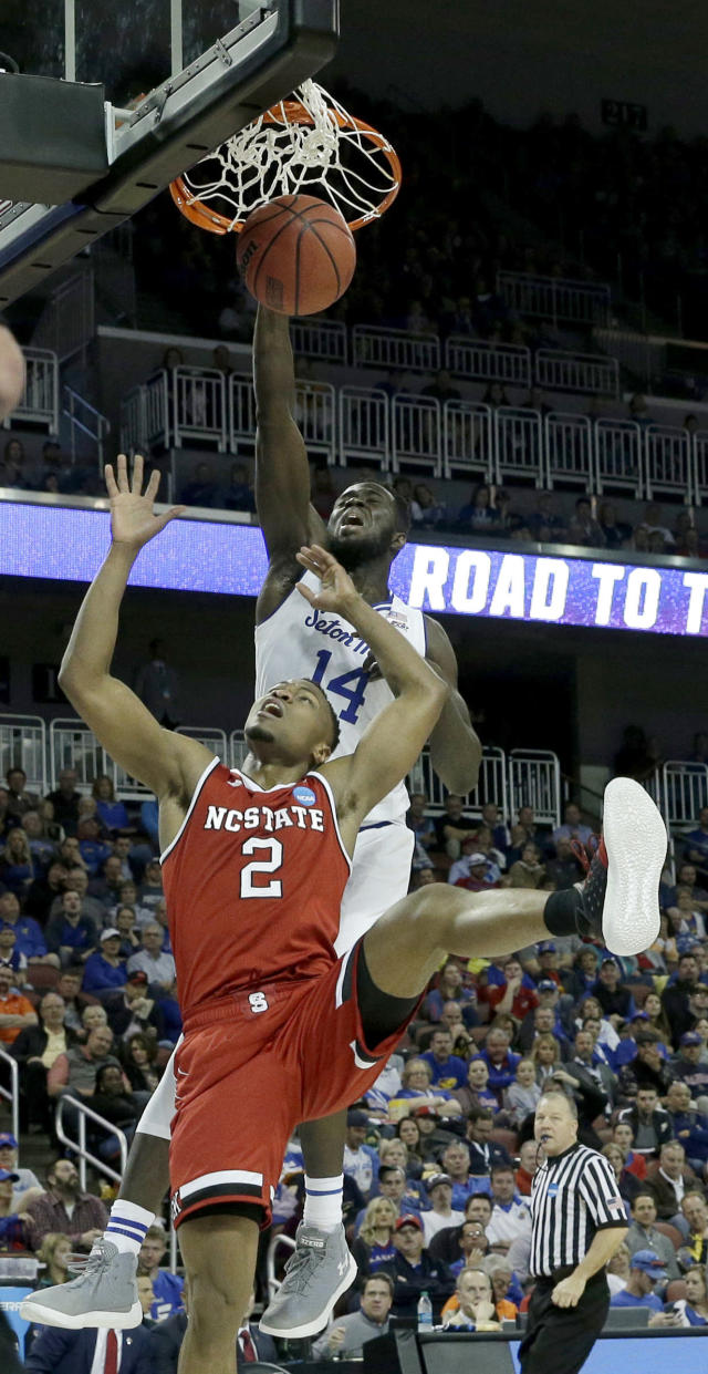Seton Hall forward Ismael Sanogo (14) dunks the ball over North Carolina State guard Torin Dorn (2) during the first half of an NCAA college basketball tournament first-round game Thursday, March 15, 2018, in Wichita, Kan. (AP Photo/Charlie Riedel)
