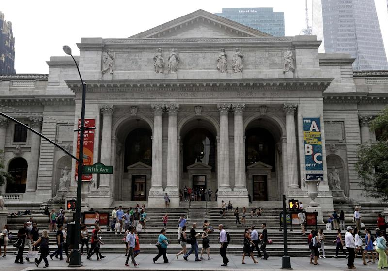In this Monday, July 22, 2013 photo, pedestrians walk past the main branch of the New York Public Library in New York, Monday, July 22, 2013. Plans for a major change within the New York Public Library's landmark main building have kindled an intellectual culture clash over its direction and the future of libraries themselves. (AP Photo/Seth Wenig)