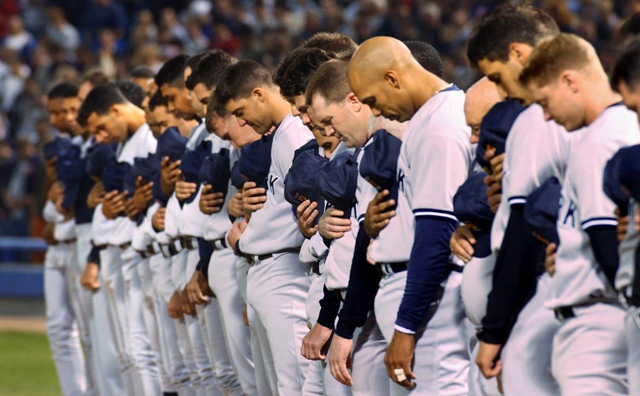 The New York Yankees bow their heads during a moment of silence in memory of those killed in the World Trade Center Attack prior to game between the Chicago White Sox, Tuesday, Sept. 18, 2001, in Chicago. (AP Photo/Stephen J. Carrera)
