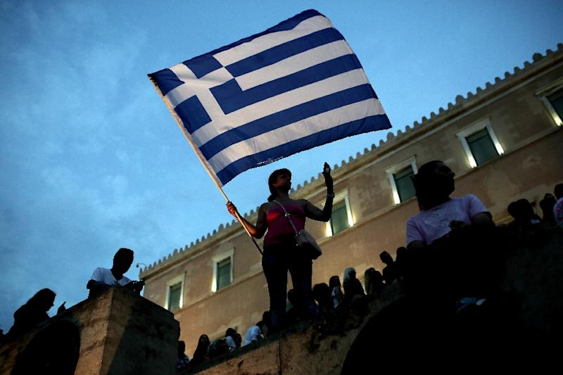 An anti-austerity protester holds a Greek flag in front of the parliament during a protest against austerity policies in Athens on June 21, 2015 (AFP Photo/Angelos Tzortzinis)