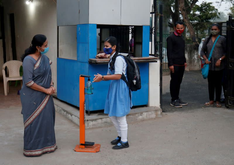 FILE PHOTO: A student sanitizes her hands upon arrival in the school to attend her class after authorities reopened schools for classes for 10 and 12, in Ahmedabad