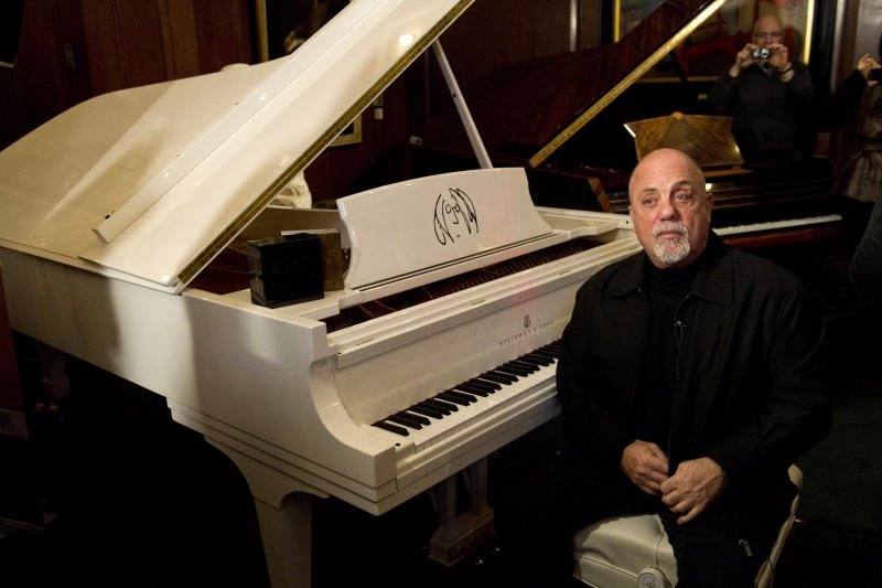 FILE - In this Dec. 12, 2011 file photo Billy Joel poses at a piano in New York. Joel, Carlos Santana, jazz artist Herbie Hancock and opera star Martina Arroyo, are the four musicians who will receive this year's Kennedy Center Honors, along with actress Shirley MacLaine. The Kennedy Center for the Performing Arts announced the selections Thursday. (AP Photo/Charles Sykes, File)