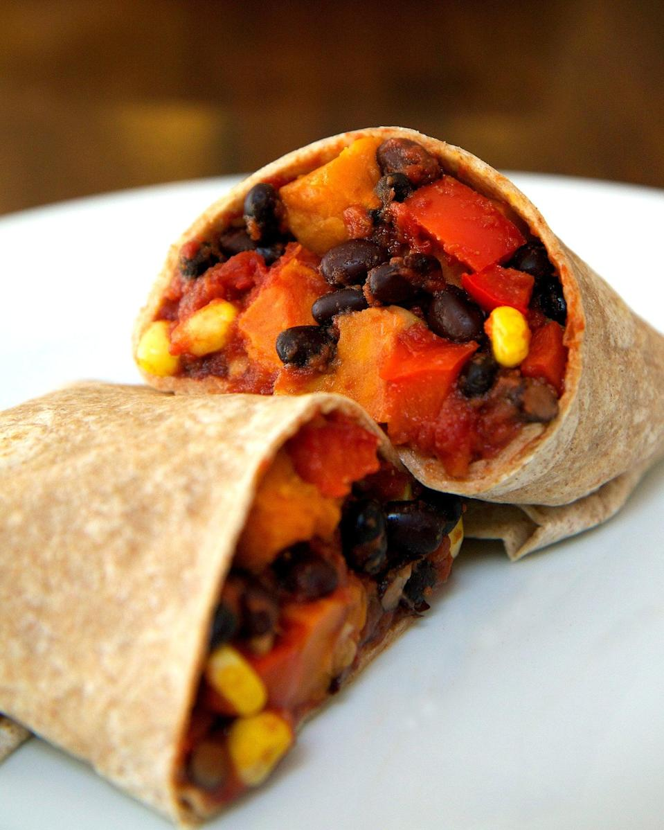 """<p>Sweet potatoes swirling with tender black beans and corn, succulent red peppers, and juicy tomatoes wrapped in a warm whole-wheat tortilla make this one delicious and gratifying meal. You can steam the sweet potatoes or <a href=""""https://www.popsugar.com/fitness/How-Cook-Sweet-Potatoes-Slow-Cooker-44111930"""" class=""""link rapid-noclick-resp"""" rel=""""nofollow noopener"""" target=""""_blank"""" data-ylk=""""slk:cook them in a slow-cooker"""">cook them in a slow-cooker</a> so no oven needed!</p> <p><strong>Get the recipe:</strong> <a href=""""http://www.popsugar.com/fitness/Vegan-Sweet-Potato-Black-Bean-Burrito-33359717/"""" class=""""link rapid-noclick-resp"""" rel=""""nofollow noopener"""" target=""""_blank"""" data-ylk=""""slk:roasted sweet potato and black bean burrito"""">roasted sweet potato and black bean burrito</a></p>"""