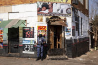 A policeman guards a liquor store in Johannesburg, Sunday, July 11, 2021 during protests in the area. Protests have spread from the KwaZulu Natal province to Johannesburg against the imprisonment of former South African President Jacob Zuma who was imprisoned last week for contempt of court. (AP Photo/Yeshiel Panchia)