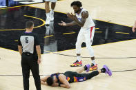 Los Angeles Clippers guard Patrick Beverley, top, reacts after being called for a foul on Phoenix Suns guard Devin Booker, bottom, during the second half of Game 2 of the NBA basketball Western Conference Finals, Tuesday, June 22, 2021, in Phoenix. (AP Photo/Matt York)