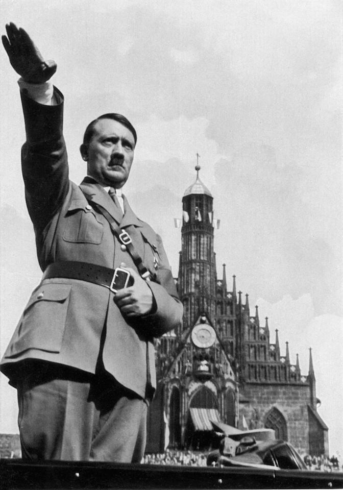 1934:  German dictator Adolf Hitler (1889-1945) giving the Nazi salute from his car whilst at the Nazi Party Congress.  (Photo by Hulton Archive/Getty Images)