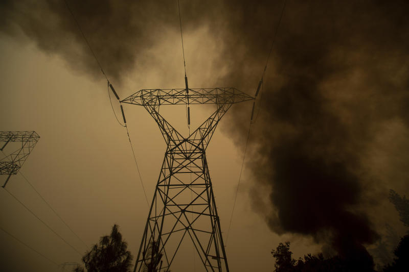 This type of power infrastructure hasn't been properly maintained by PG&E, the lawsuit claims. Here, smoke billows around power transmission lines in Big Bend, California, on Friday. (Noah Berger/ASSOCIATED PRESS)