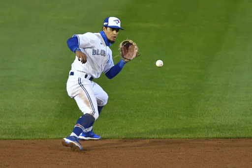 Toronto Blue Jays shortstop Santiago Espinal fields a ground ball by New York Mets' Wilson Ramos who was out at first during the sixth inning of a baseball game in Buffalo, N.Y., Friday, Sept. 11, 2020. (AP Photo/Adrian Kraus)