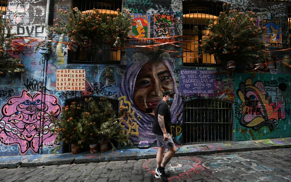 A man walks past a floral display along Hosier Lane in Melbourne as the state starts easing its emergency restrictions by allowing people outdoors without wearing a mask for the first time in months - ERIK ANDERSON/EPA-EFE/Shutterstock