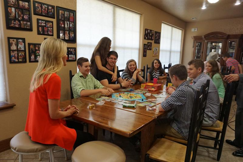 The Duggar family sitting at the dining table together