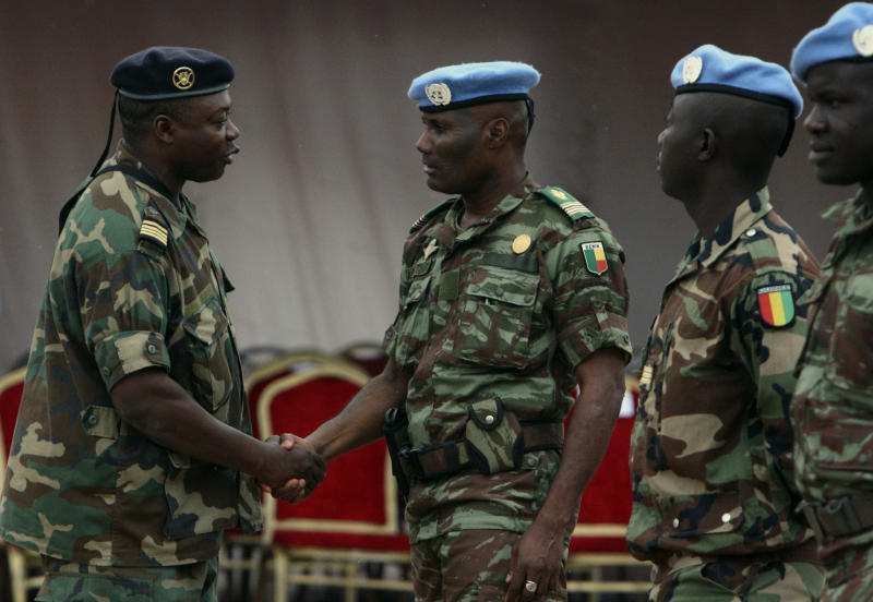 A military chief, left, shakes the hands of African troops who helped France take back control of Mali's north earlier this year, during a ceremony formally transforming the force into a United Nations peacekeeping mission, in Bamako, Mali, Monday, July 1, 2013. The roughly 6,000 African troops will be folded into the Integrated United Nations Mission for the Stabilization of Mali, or MINUSMA, which is expected to grow to more than 12,000 soldiers. (AP Photo/Harouna Traore)