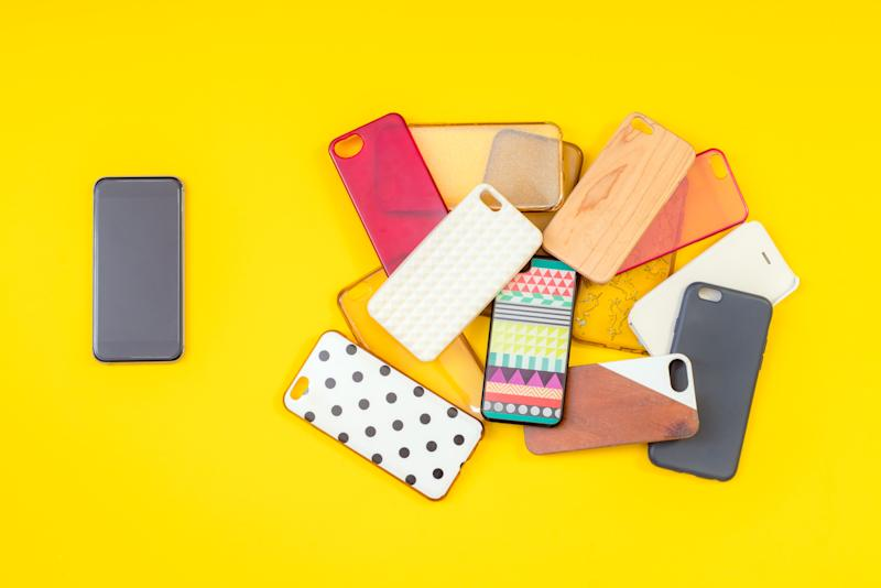 Pile of multicoloured plastic back covers for mobile phones on yellow background with a phone on the side