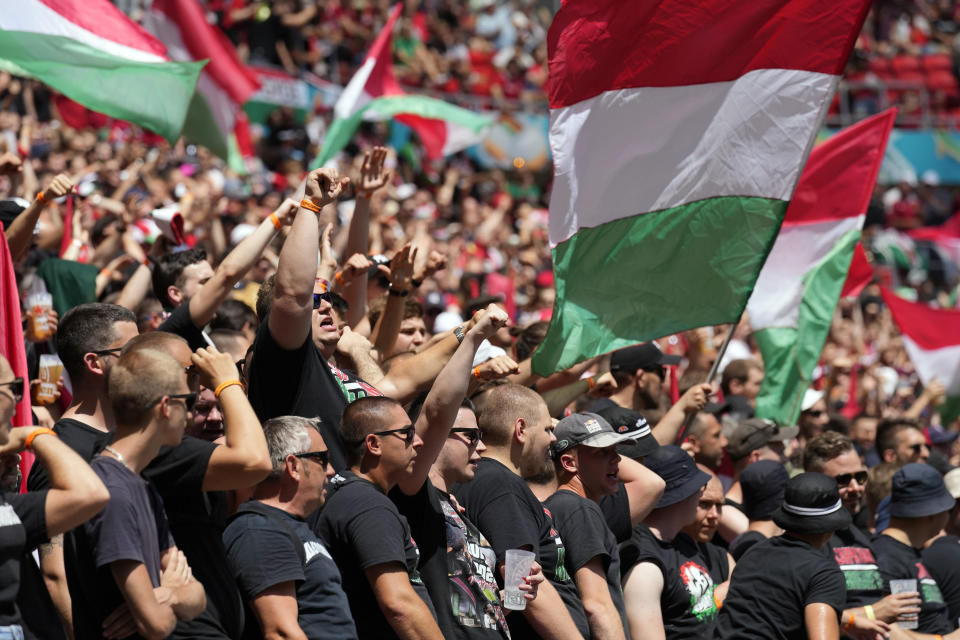 Hungarian fans wave their national flags prior to the Euro 2020 soccer championship group F match between Hungary and France, at the Ferenc Puskas stadium in Budapest, Saturday, June 19, 2021. (AP Photo/Darko Bandic, Pool)